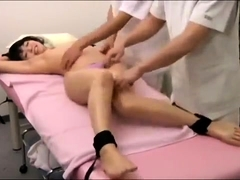 Adorable Japanese girl is made to cum on the massage table