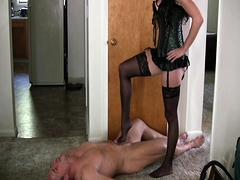 Slender dominatrix in stockings works her feet on a cock