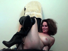 Big breasted cougar in black boots pleases herself on webcam