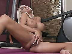 Tanned mommy with big fake tits rubs her pussy