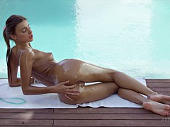 Slim babe has solo fun by the pool
