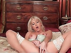 Sultry blonde masturbates in lace top stockings